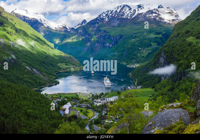 High view over Geirangerfjorden surrounded by snowcapped mountains in summer. Geiranger, Sunnmøre, Møre - Stock Image
