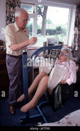 Husband lifting  ill wife with a hoist - Stock Image