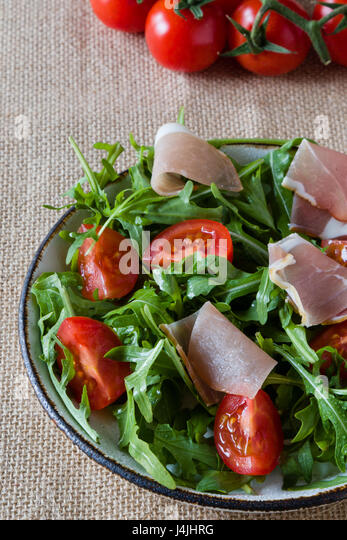 fresh healthy ruccola salad with tomato and ham - Stock Image