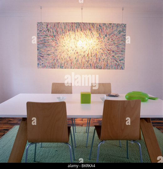 Lighting Above Abstract Painting On Wall Of Modern Dining Room With White MDF Table And Pale