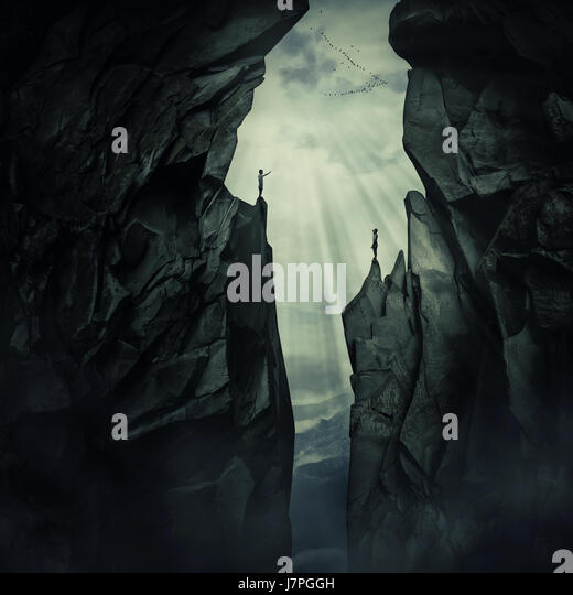 Conceptual image with two lost persons standing on the edge of different mount peaks, trying to find each other. - Stock Image