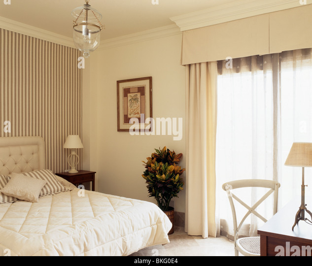 Striped wallpaper behind bed with cream quilt in Spanish bedroom with cream  curtains at French windows. Interiors Bedrooms Wallpaper Quilts Stock Photos   Interiors