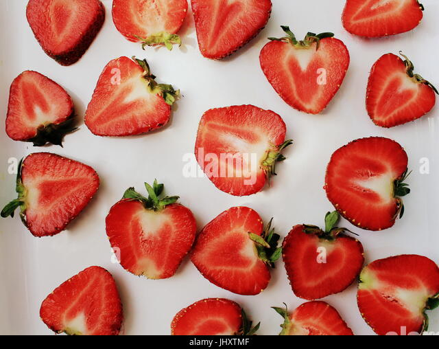 Strawberry creative pattern. Isolated food backdrop. Sliced ripe red berry with green leaves on white background - Stock Image