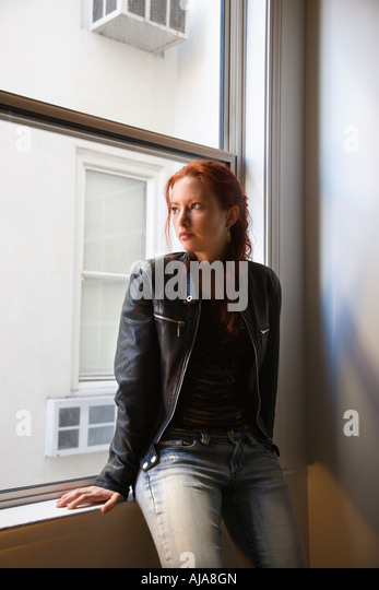 pretty redhead young woman sitting indoors on window ledge looking out stock image