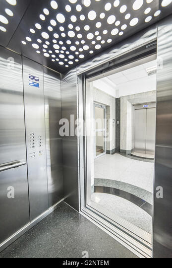interior of a modern elevator - shiny steel and lighting - Stock Image