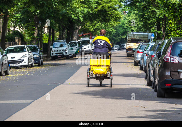 German Postman posting a bicycle mail, Dresden, Germany, Europe - Stock Image