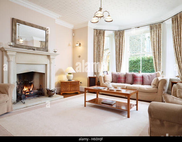 A Large Traditional Homely Victorian Livingroom With An Impressive Fireplace And Roaring Fire UK