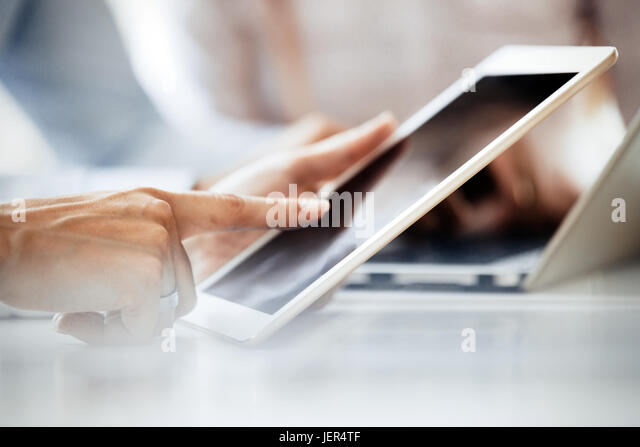 Close up picture of businessman using tablet on office desk - Stock Image