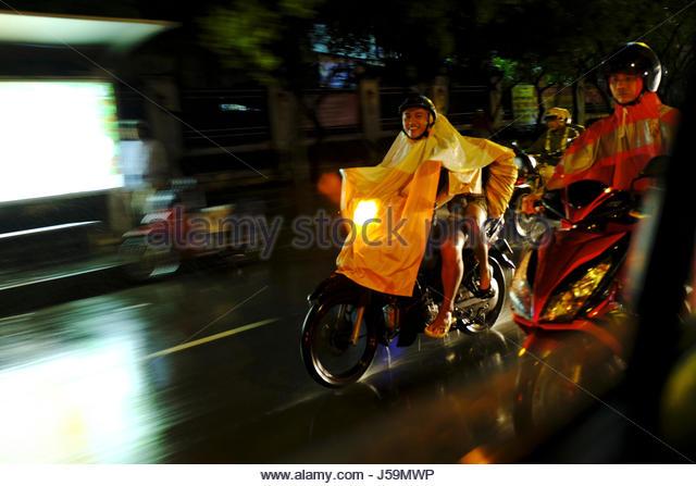Night shot of speeding motorbike in the rain in Saigon, Vietnam - Stock Image