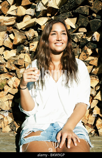 Girl by a stack of wood - Stock Image