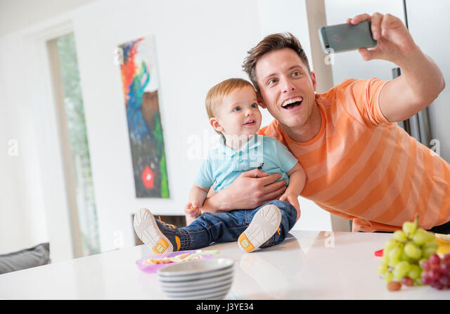 father and toddler son taking selfie in kitchen at home - Stock Image