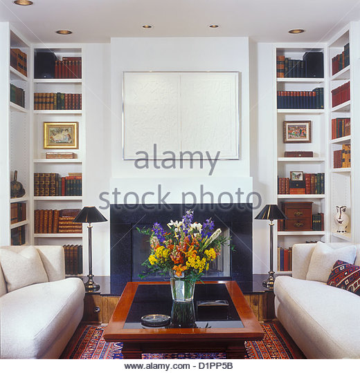 Floor to ceiling bookshelves in cream living stock photos for Area in front of fireplace