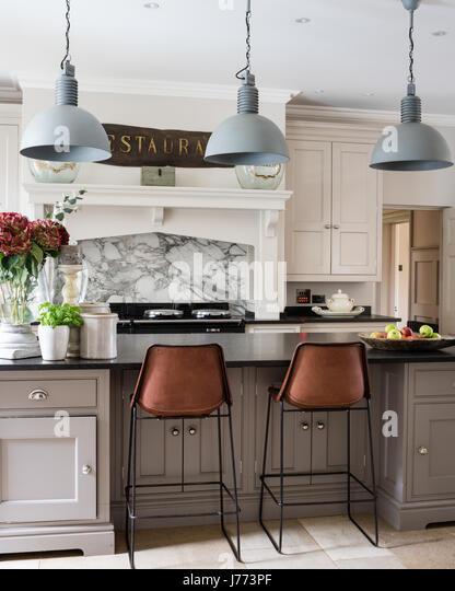 Pendant lights by Bardoe & Appela bove kitchen breakfast bar. The Sol y Luna bar stools are from Bardoe & - Stock Image