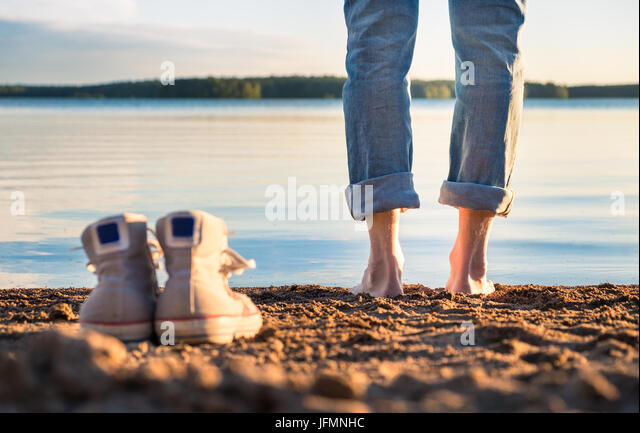 Man standing in beach at nice summer evening in Finland. - Stock Image