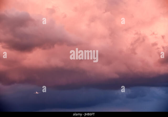 Commercial jet airliner taking off into heavy weather from Atlanta International Airport under ominous sunset-painted - Stock Image