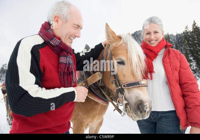 Italy, South Tyrol, Seiseralm, Senior couple standing by horse ...