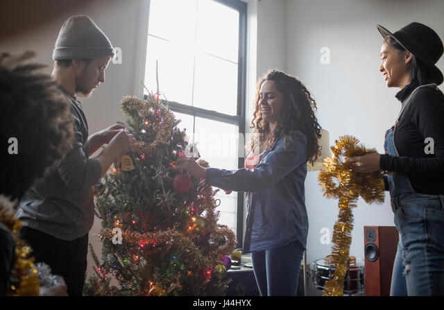 A group of people decorating a Christmas tree - Stock Image