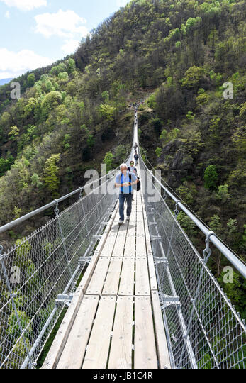 Sementina, Switzerland: people walking on the suspension bridge over the valley at Semerntina on the Swiss alps - Stock Image