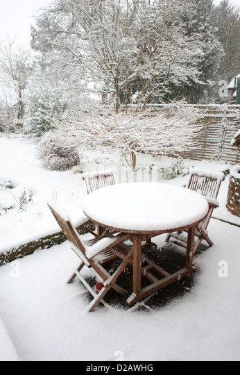 Garden furniture with a covering of snow in a Hampshire garden UK   Stock  Image. Garden Table Chairs Covered In Stock Photos   Garden Table Chairs