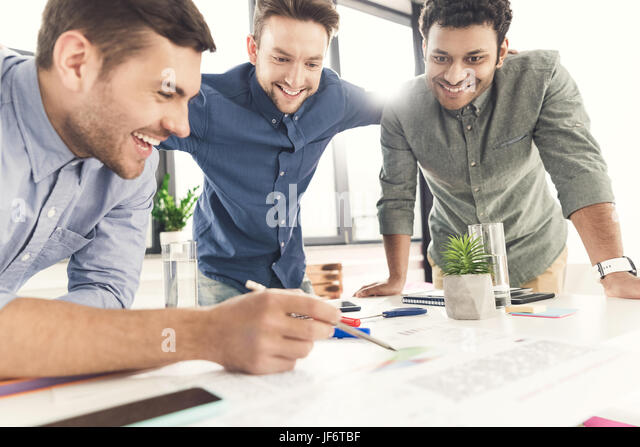 Three young businessmen leaning at table and working at project together, business teamwork concept - Stock Image
