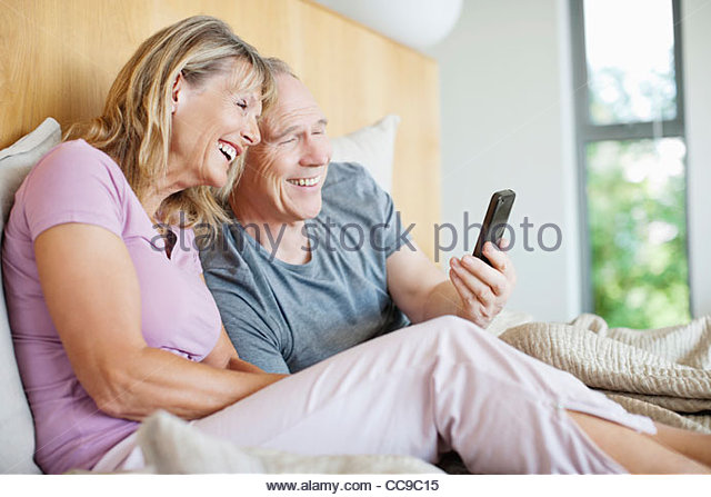 Couple bed phone stock photos couple bed phone stock for Cell phone bed