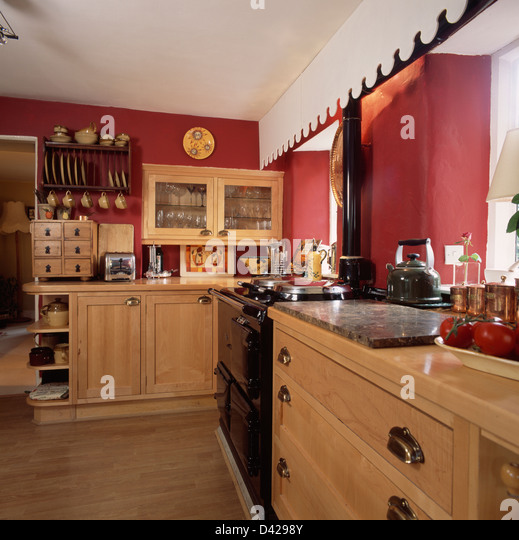 Black Aga And Pale Wood Fitted Units In Red Country Kitchen Stock Image