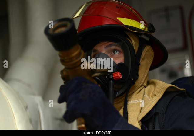 us navy intelligence specialist 3rd class dustin truax simulates fire fighting techniques aboard the aircraft navy intelligence specialist