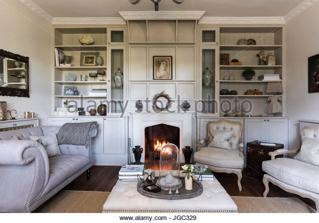 Lit Fire With Buttoned Sofas And Recessed Shelving