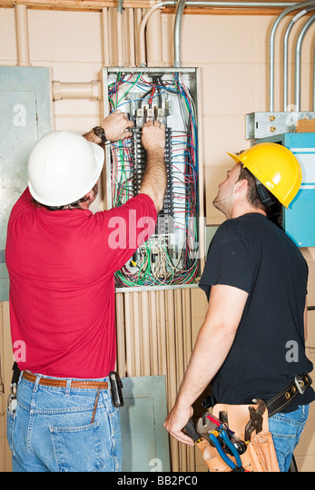 electrician and apprentice changing out a faulty circuit breaker in bb2pc0 faulty electrical fuse box stock photos & faulty electrical fuse faulty fusebox switches at crackthecode.co
