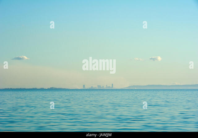 The Brisbane city skyline viewed from across the pastel ocean surface. - Stock Image