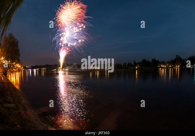 Fireworks on the river Ticino in a summer evening with landscape in the background, final of the show - Stock Image