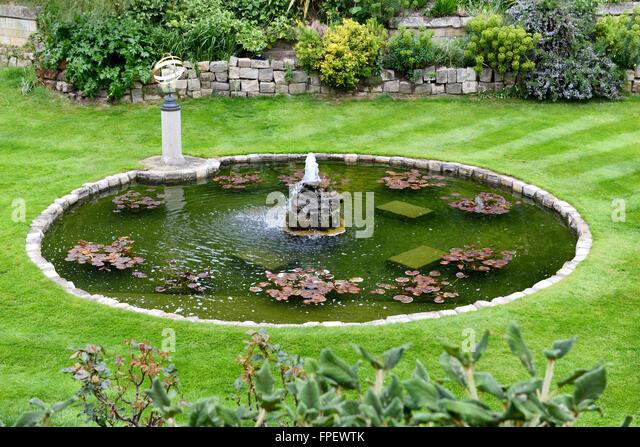 Stone fountain in circular pond stock photos stone for Circular garden ponds