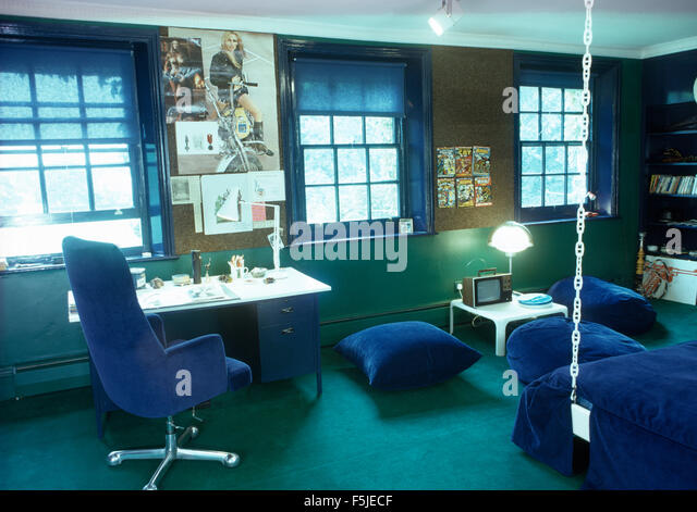 blue velvet chair and floor cushions in a sixties bedroom stock image