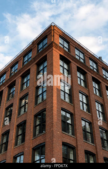 Exceptional Low Angle View Of Tall Brick Apartment Building With Beautiful Blue Sky And  Clouds Reflecting In