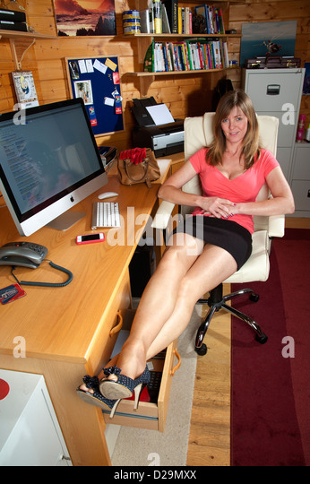 woman taking a break from her office chores stretching her legs at the desk her - Office Chair For Short Person