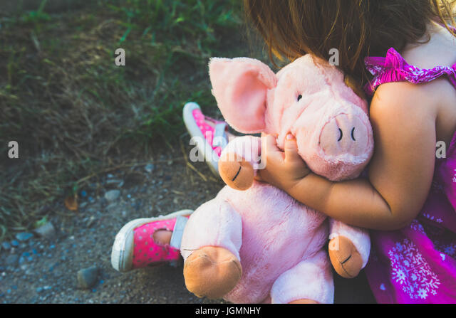 A little girl holds a stuffed pink pink - Stock Image