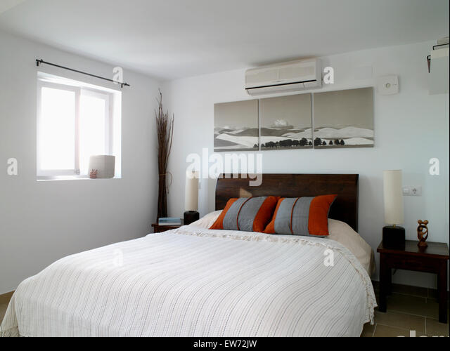 Air Conditioning Unit And Large Picture Above Bed With Gray+red Cushions  And Cream