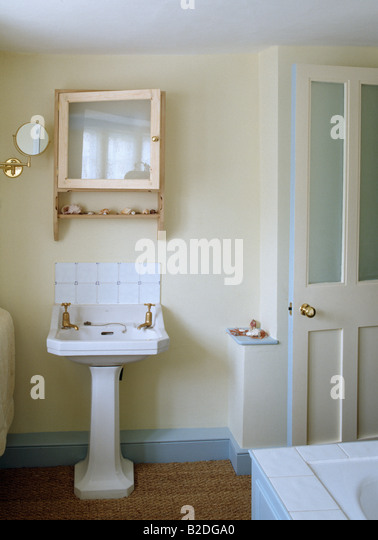 White pedestal basin below mirrored pine cabinet in cream bathroom with  pale blue skirting boards and. Skirting Boards Stock Photos   Skirting Boards Stock Images   Alamy