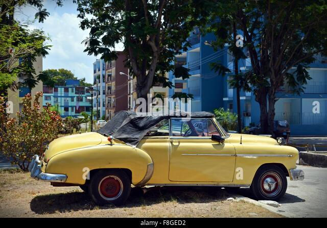 beat up vintage yellow soft top car parked badly in a residential street in havana cuba