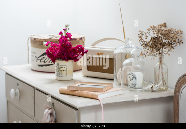 Roberts radio and glass bell jars on upcycled chest of drawers painted in Annie Sloan's Old White and Country - Stock Image