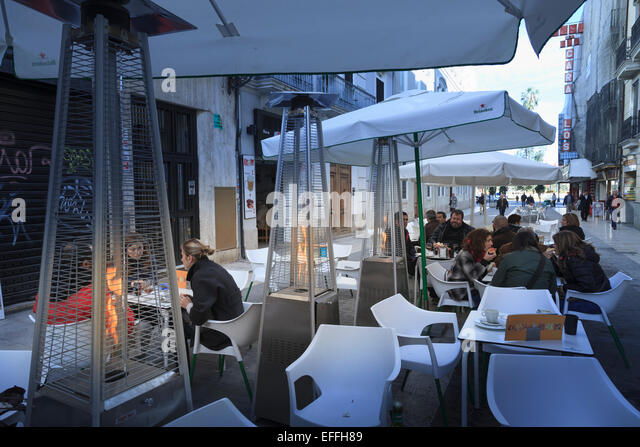 Customers At A Street Cafe In Winter Valencia With Patio Flame Heaters    Stock Image