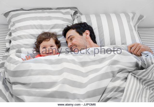 Smiling man and baby girl lying in bed under stripy duvet. - Stock Image