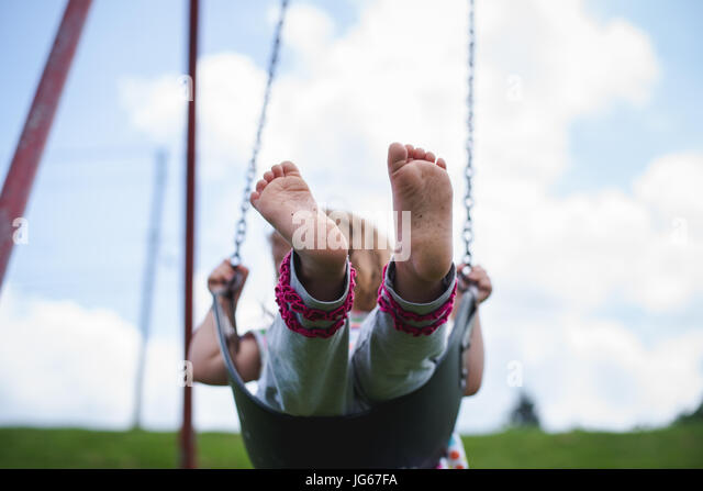 A child plays at a playground - Stock Image