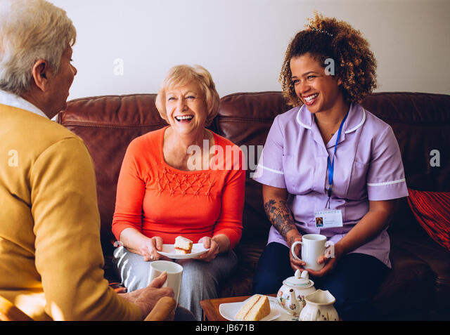 Elderly carer sitting with two of her patients in the care home. They are enjoying some cake and tea. - Stock Image