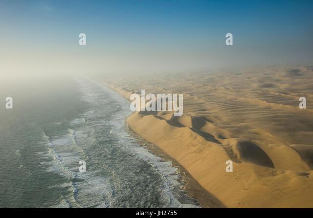 Aerials of sand dunes of the Namib Desert meeting the Atlantic Ocean, Namibia, Africa - Stock Image