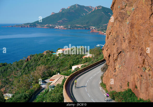 CYCLISTS ON THE SCENIC 'CORNICHE D'OR' BETWEEN THE RED VOLCANIC ROCK AND THE AZURE MEDITERRANEAN SEA. - Stock Image