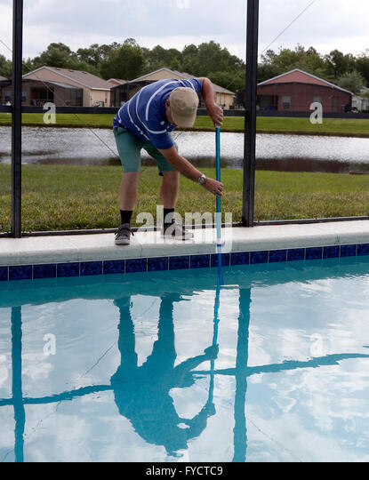 Mature man doing pool maintenance to his Florida pool home, 25th April 2016  - Stock