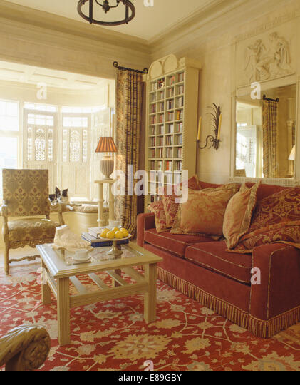 Patterned Cushions On Dark Red Sofa With Fringed Edging In Cream Living Room And
