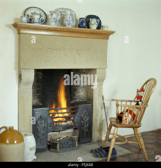 Windsor Chair Beside A Stone Fireplace With Lighted Fire In Country Dining Room
