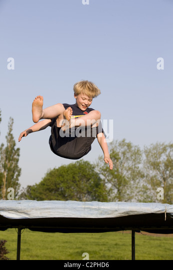 young boy jumping on trampoline smiling at camera hot